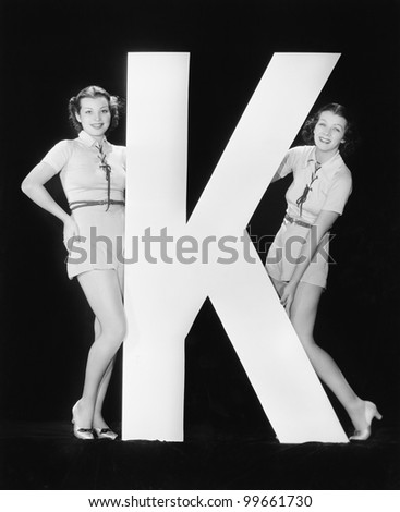Women posing with huge letter K - stock photo