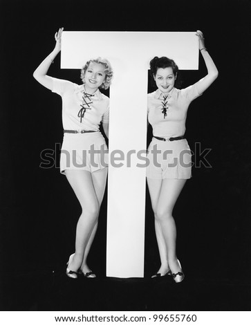 Women posing with huge letter T - stock photo
