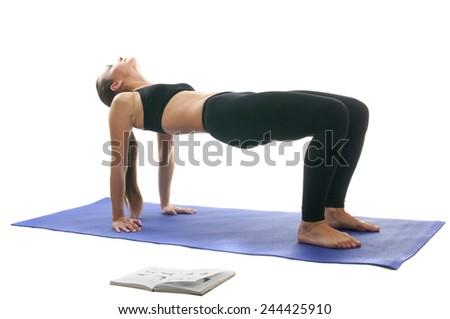 Women practice yoga with book: table asana - stock photo