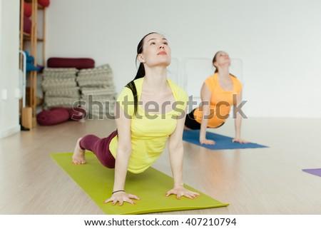women practicing the Bhujangasana (Cobra Pose) - stock photo