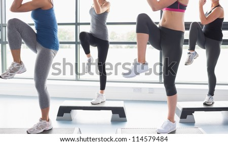 Women raising their legs while doing aerobics in gym - stock photo
