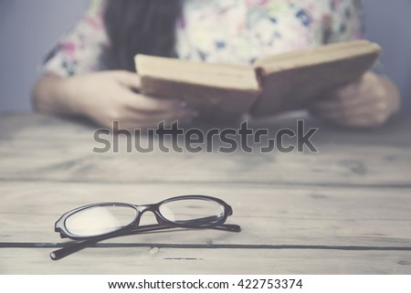 women read a book on wood table - stock photo