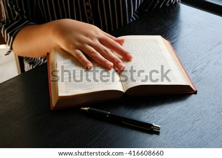 women read book on wooden table ,hand writing pen on paper page,hardworking for achievement business target concept, reading book for knowledge concept.
