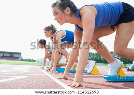 Women ready to race on track field - stock photo