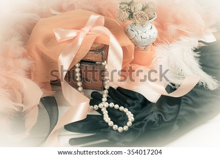 Women retro accessories including velvet gloves and pearl necklace on wooden  table - stock photo