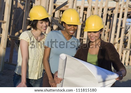 Women reviewing blueprint at construction site - stock photo