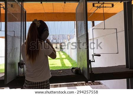 Women rifle shooting in the indoor Shooting Range. - stock photo
