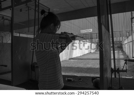 Women rifle shooting in the indoor Shooting Range black and white tone. - stock photo