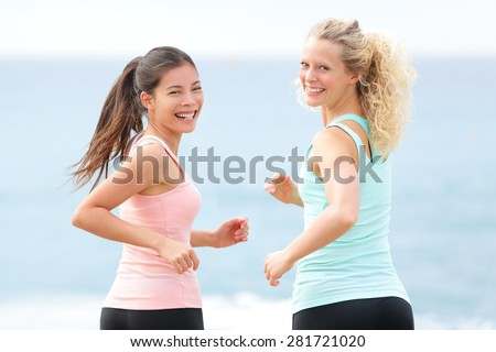 Women running exercising. Two young fit female friends runners smiling jogging on summer beach enjoying healthy lifestyle. Beautiful fitness models turning towards camera in summer. - stock photo