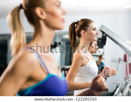 women running on a treadmill in a fitness club, sport in the fitness club - stock photo