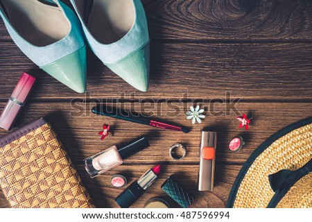 women's accessories - bag, heels, earrings, nail polish, lipstick on wooden background, top view