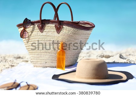 Women's beach accessories on sand for summer vacation concept. Straw tote bag, sun hat and sunscreen lotion or suntan tanning oil spray bottle with blue ocean background for travel holidays. - stock photo