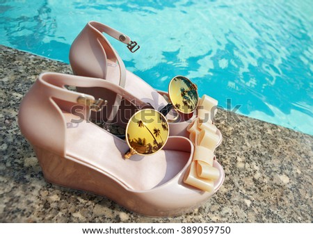 Women's beach wedges with glasses by the pool - stock photo