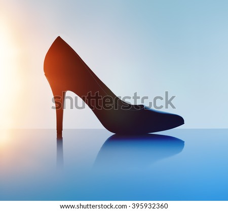 Women's black pump shoe in silhouette and with lens flare. - stock photo