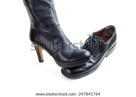 "Women's boots and men's shoes - symbolizes the saying ""a man under the influence of his wife"" on white background - stock photo"