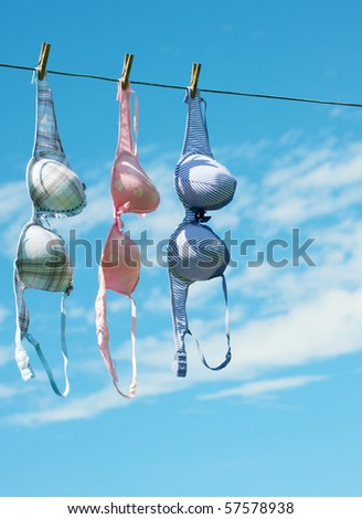 Women's bras hang in the fresh air and sunshine drying with copy space. - stock photo