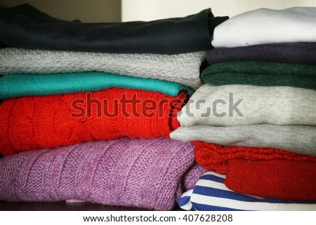 Women's clothing folded on a shelf in the closet. Knitted sweaters, T-shirts, polo. - stock photo