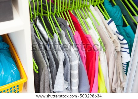 Women's clothing hanging on hangers. Colored jackets and sweaters. Hangers in a row.