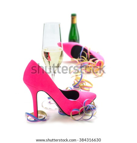 women's day party, ladies pink high heels shoes, streamers, champagne glass and bottle, isolated on a white background, concept for valentines or mother's day, selected focus, narrow depth of field - stock photo