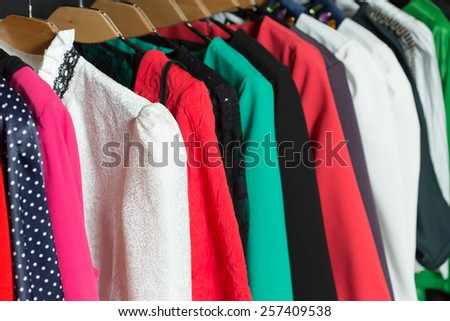 women's dresses on hangers in a retail shop - stock photo