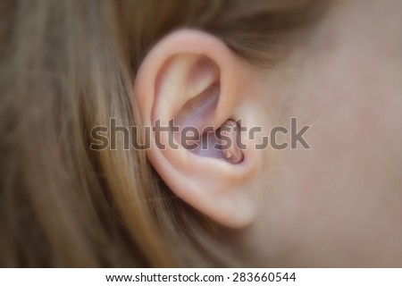 Women's ear with a hearing aid - stock photo