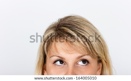 women's eyes peek out from behind framework - stock photo