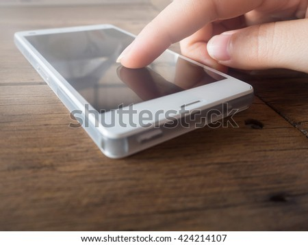 Women's finger touching  smart phone screen on wooden table