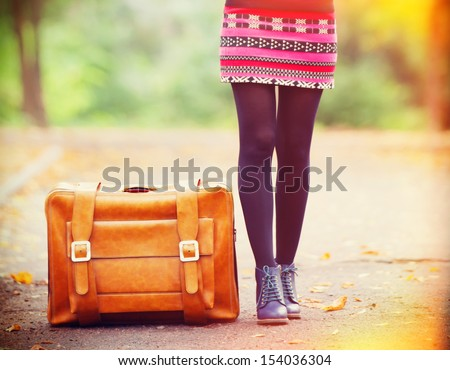 Women's foots near suitcase at autumn outdoor. - stock photo