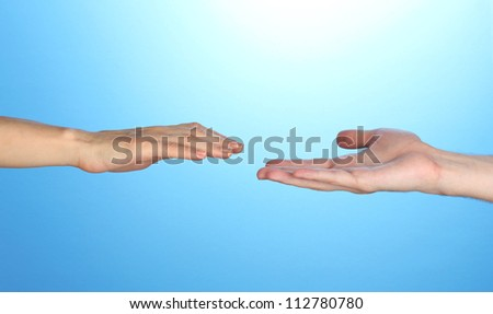 Women's hand goes to the man's hand on blue background