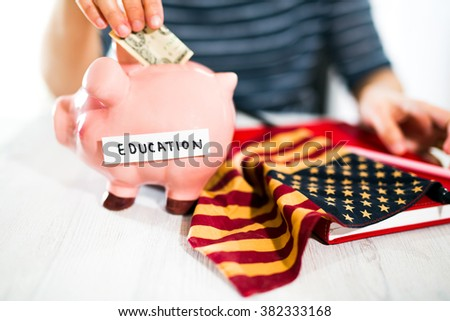 Women's hand puts money in piggy bank.Selective focus. Saving for a education