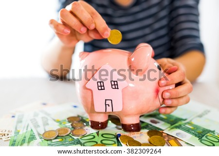 Women's hand puts money in piggy bank. Selective focus. Saving for a house