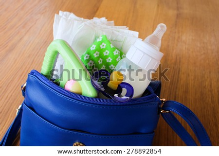 Women's handbag with items to care for the child: bottle of milk, disposable diapers, rattle, pacifier and baby clothes. - stock photo