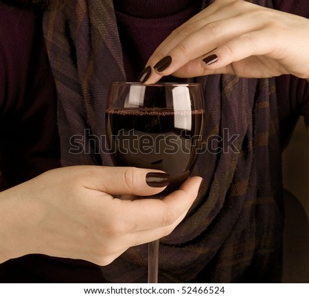 women's hands and a glass of wine on the background of cellular muffler