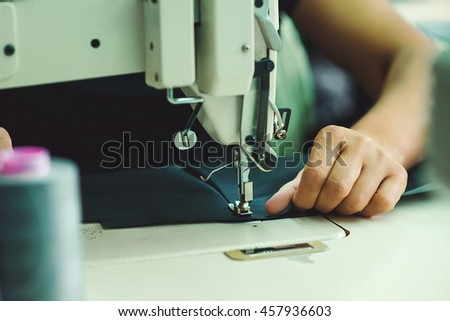 Women's hands behind her sewing.