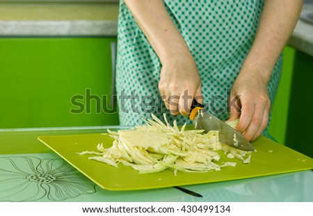 women's hands cut the cabbage on a green chalkboard