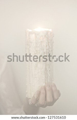 Women's hands hold a candle to the mystical image of candles - stock photo
