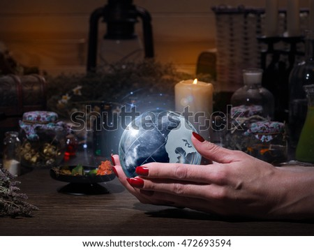 Women's hands holding the magic sphere with the stars. The blue glow ...