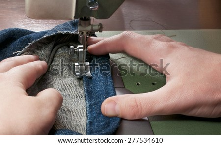 Women's hands  sew fabric with a sewing machine. Close-up - stock photo