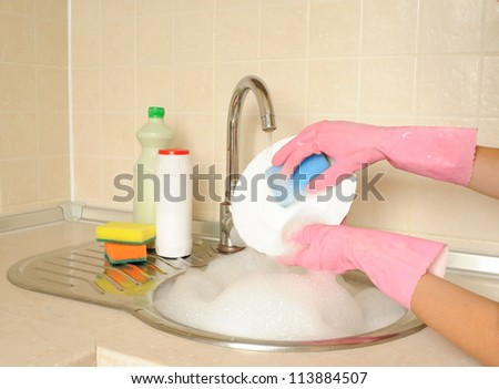 Women's hands washing dish in the kitchen