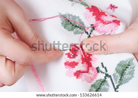 Women's hands with a cross embroidered on the fabric patterns of flowers roses - stock photo