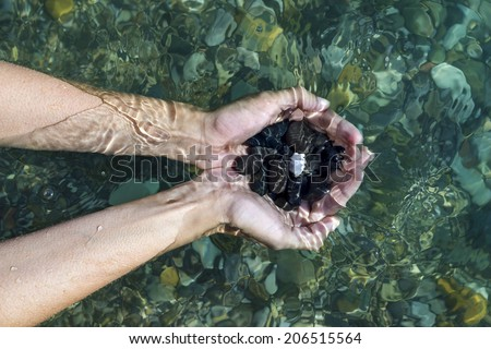 Women's hands with a handful of sea stones under water, holds in the clear sea water. Top view - stock photo