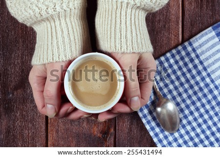 Women's hands with a hot cup of coffee. Coffee with milk, latte. A cup of coffee on the table. Embracing a cup of coffee. Cozy home atmosphere. Morning coffee. Toned image. - stock photo