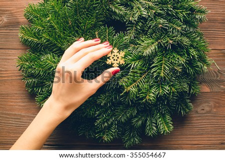 Women's hands with a red manicure holding Christmas decorations. View from above.