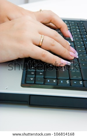 Women's hands with long nails on the laptop keyboard
