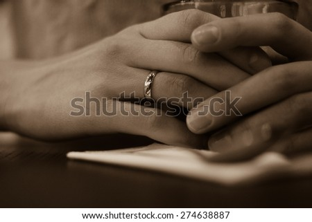 Women's hands with wedding rings close up. Hands on the table and keep a glass beaker. The ring is on her right hand. Vintage photo.