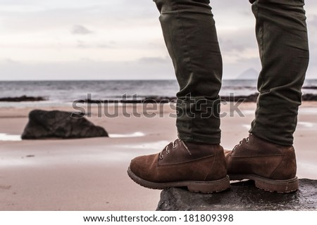 Women's 6-Inch Brown Waterproof Boots and skinny trousers on a rock with sand beach and ocean in the background. Scotland (UK) - stock photo