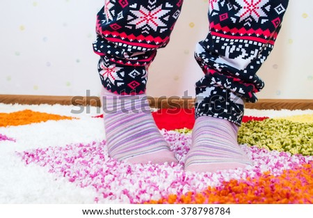 Women's legs in pajamas and socks on the bright carpet. Girl standing on the soft , colored carpet - pictured legs in pajamas and colorful socks. - stock photo