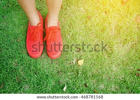 women's legs standing on green grass, relaxing background