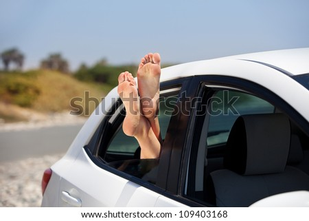 Women's legs sticking out the car window. The concept of relaxation and travel - stock photo