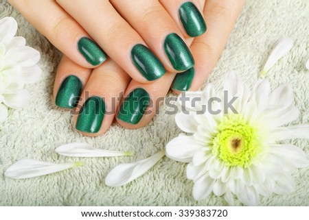 Women's manicure with effect of cat's-eye gel polish on the nails.